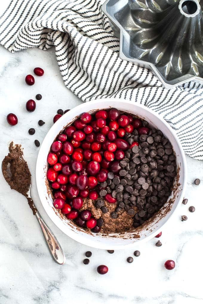Ingredients for Dark Chocolate Cranberry Bundt Cake being mixed together in a white bowl.