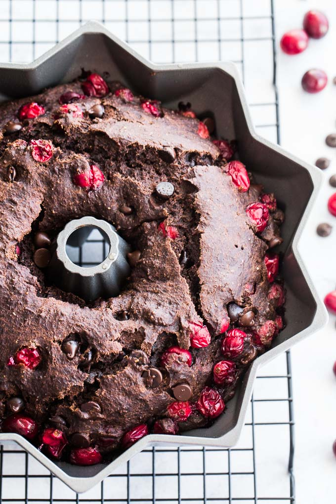 Dark Chocolate Cranberry Bundt Cake baked up in a bundt pan, cooling on a wire rack.
