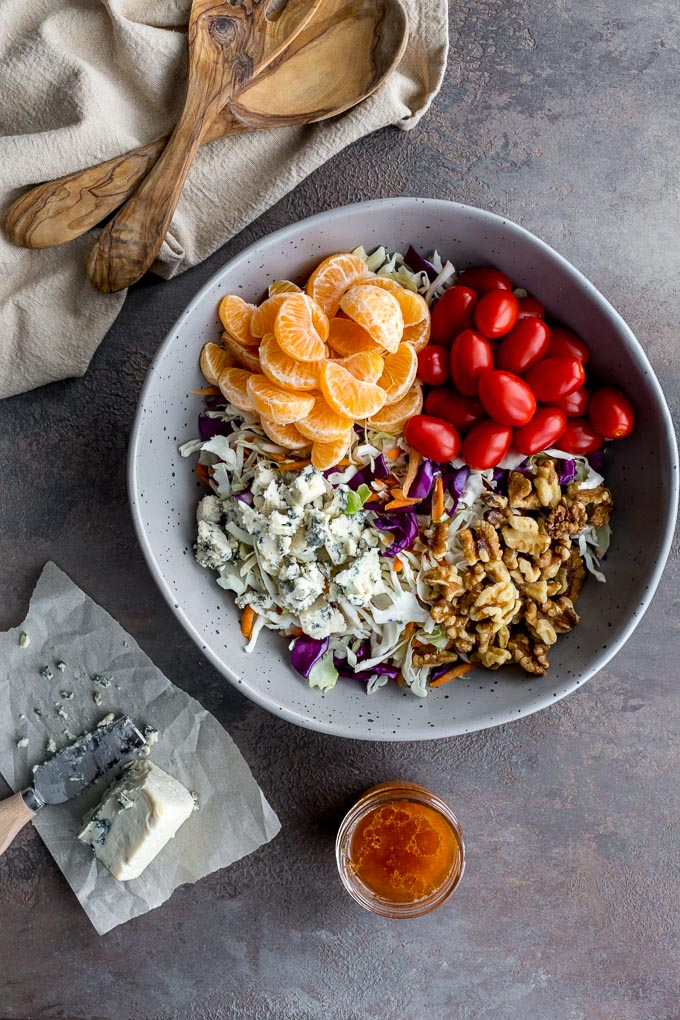 Ingredients for Citrus Crunch Salad assembled in a large grey bowl.