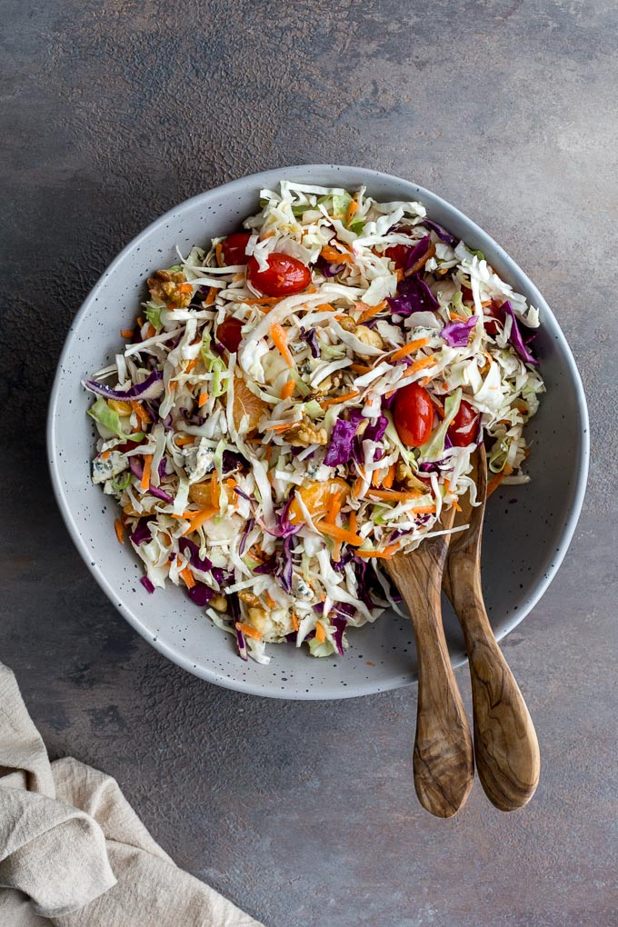 Citrus Crunch Salad mixed together in a large bowl with two wooden serving spoons.