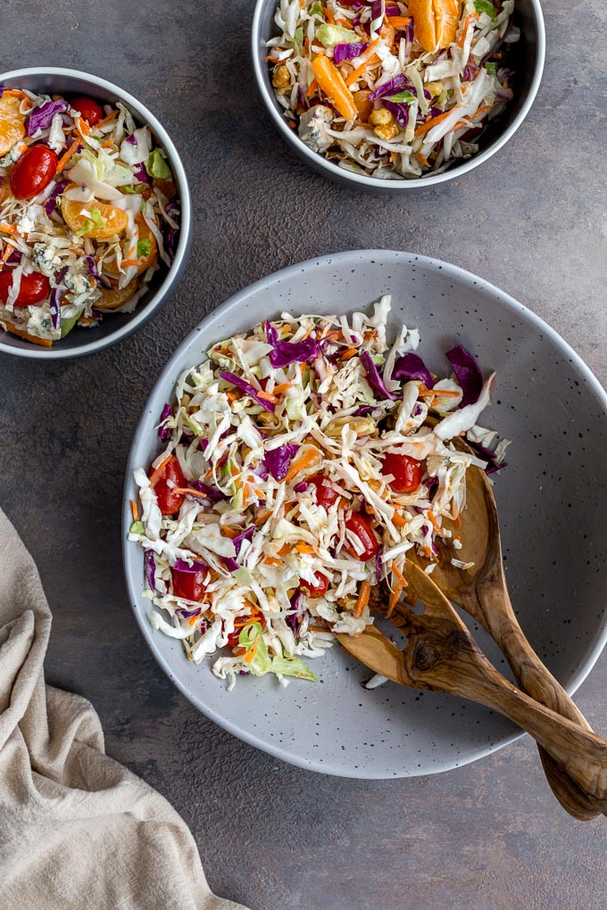 Citrus Crunch Salad in a grey bowl and served up into two smaller bowls.