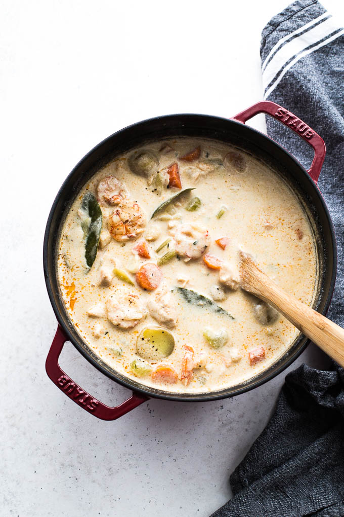 Overhead view of Dairy-Free Seafood Chowder in a red pot with a wooden spoon inserted in it.