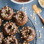 Overhead view of Peanut Butter Banana Protein Donuts topped with glaze and chopped peanuts and arranged on a wire rack.