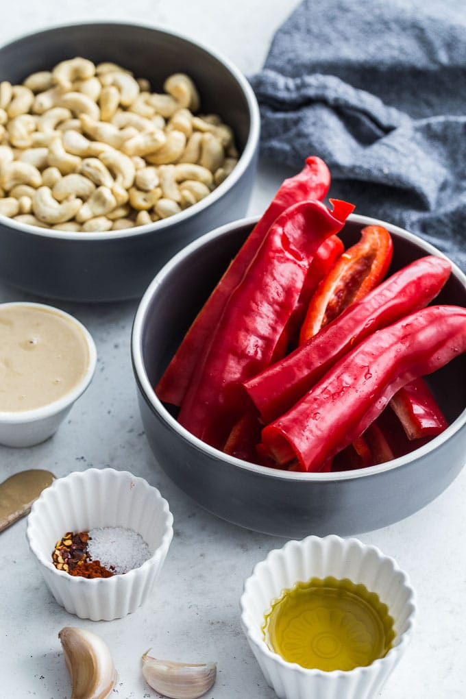 Ingredients to make vegan red pepper dip arranged in individual dishes.