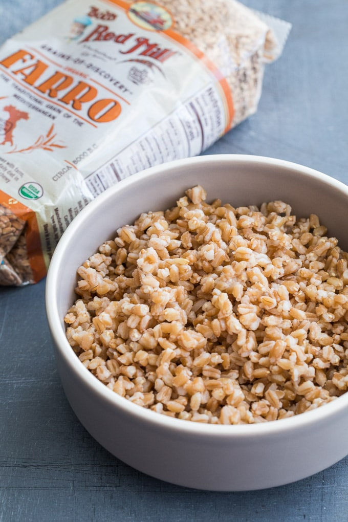 Up-close view of cooked farro in a grey bowl with a package of farro in the background.