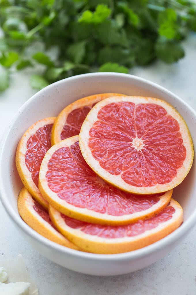 Up-close view of pink grapefruit slices in a white bowl.