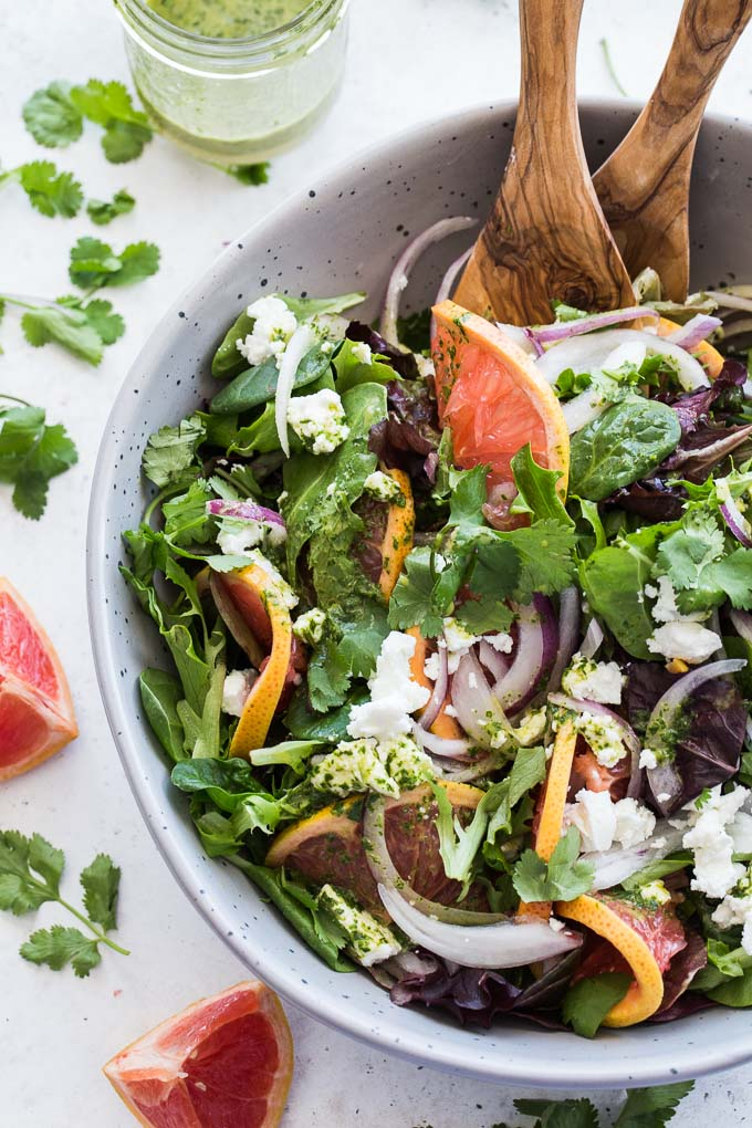 Overhead view of Grapefruit Salad with Cilantro and Goat Cheese in a grey bowl with wooden serving spoons.