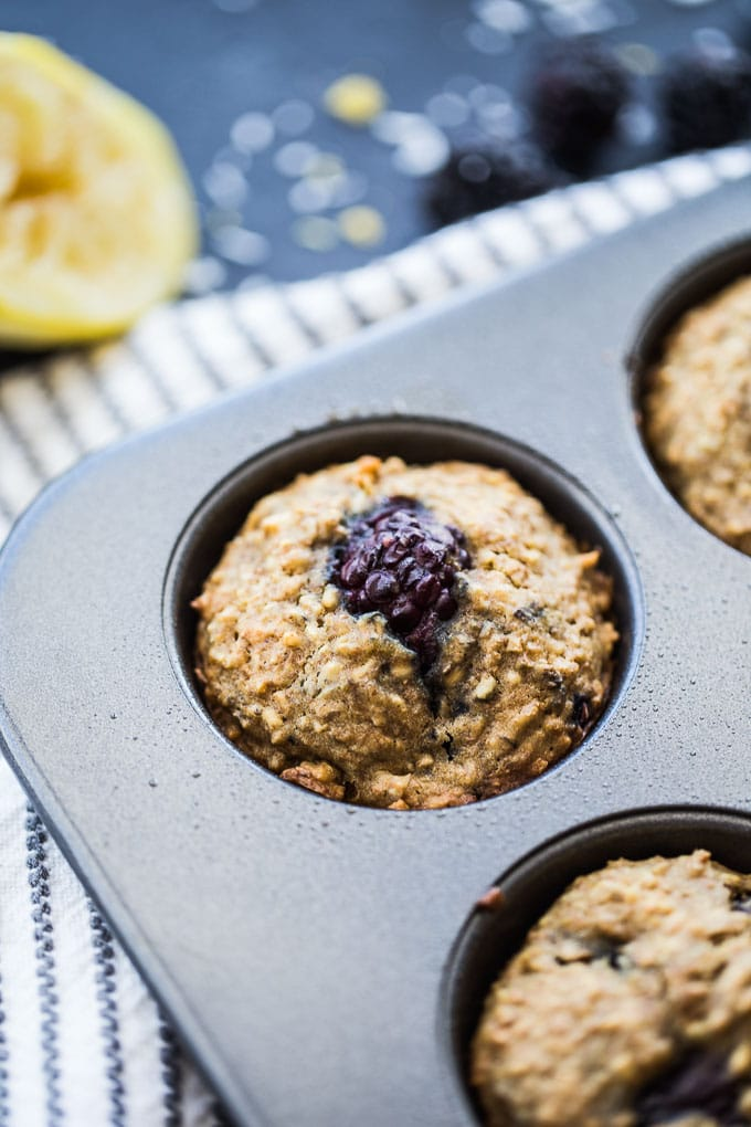 Up-close view of Blackberry Lemon Overnight Oatmeal Muffins cooling in a muffin pan.