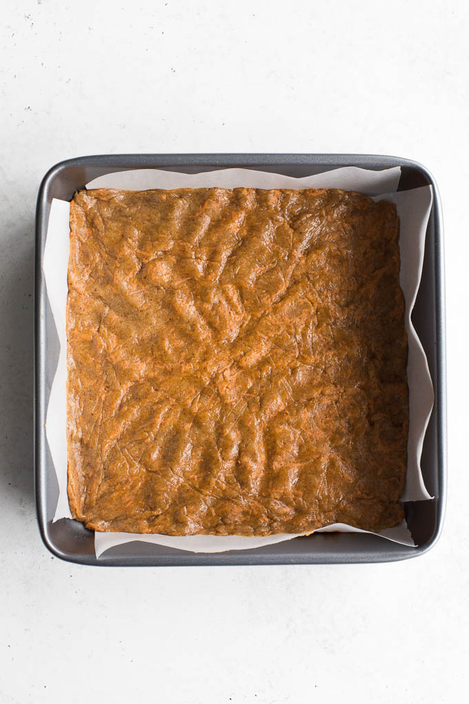Carrot cake cookie dough spread out in a square pan.