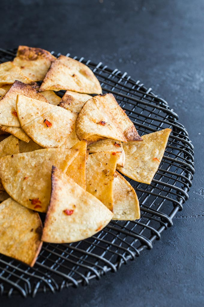 Up-close view of tortilla chips on a cooling rack on a dark surface.