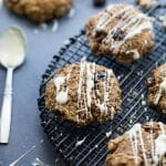 Morning Glory Breakfast Cookies on a wire rack with white chocolate drizzled on top.