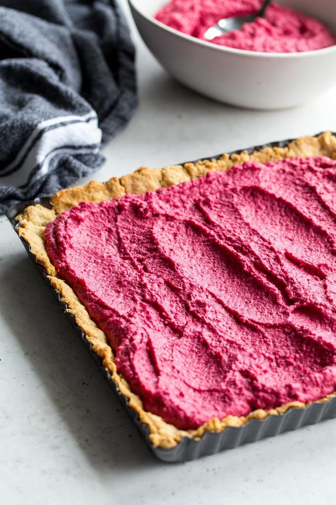 Up-close view of beet hummus spread out on an almond crust.