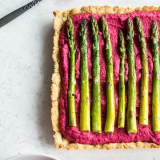 Overhead view of beet hummus asparagus tart on a light surface.