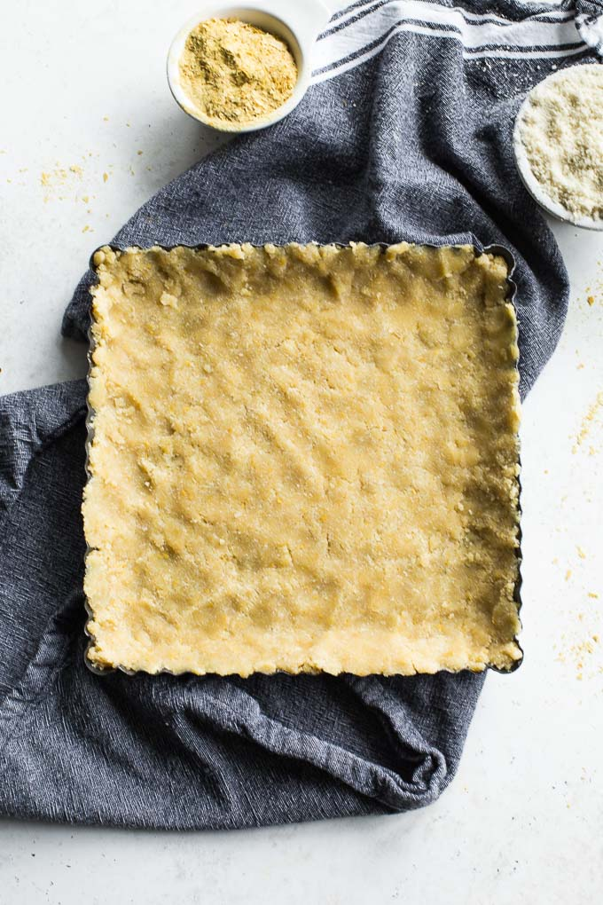 Overhead view of almond flour crust pressed into a tart pan and ready for the oven.