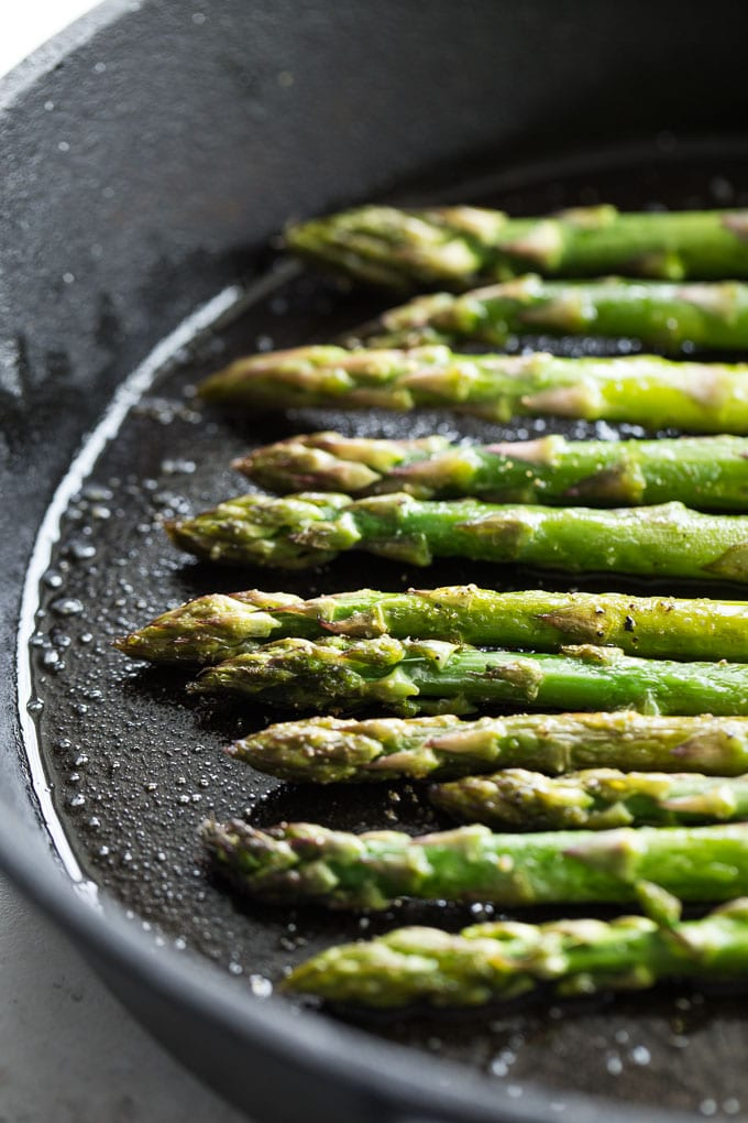 Up-close view of sauteed asparagus in a cast iron skillet.
