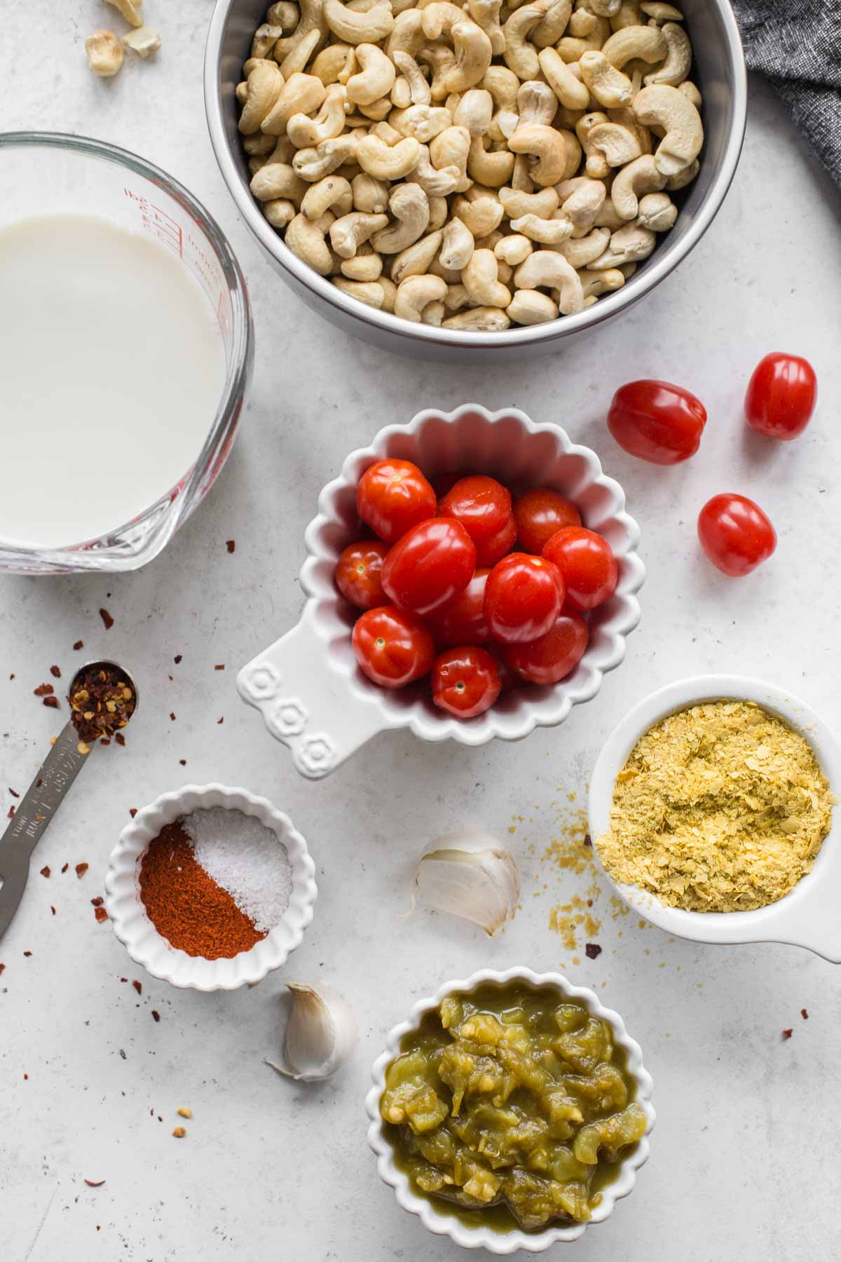 Ingredients to make dairy-free queso arranged individually on a marbled surface.