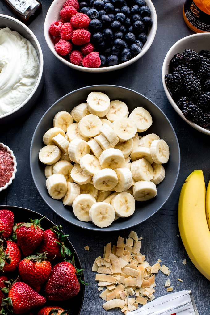 Overhead view of banana slices in a bowl, surrounded by other fruit and yogurt.