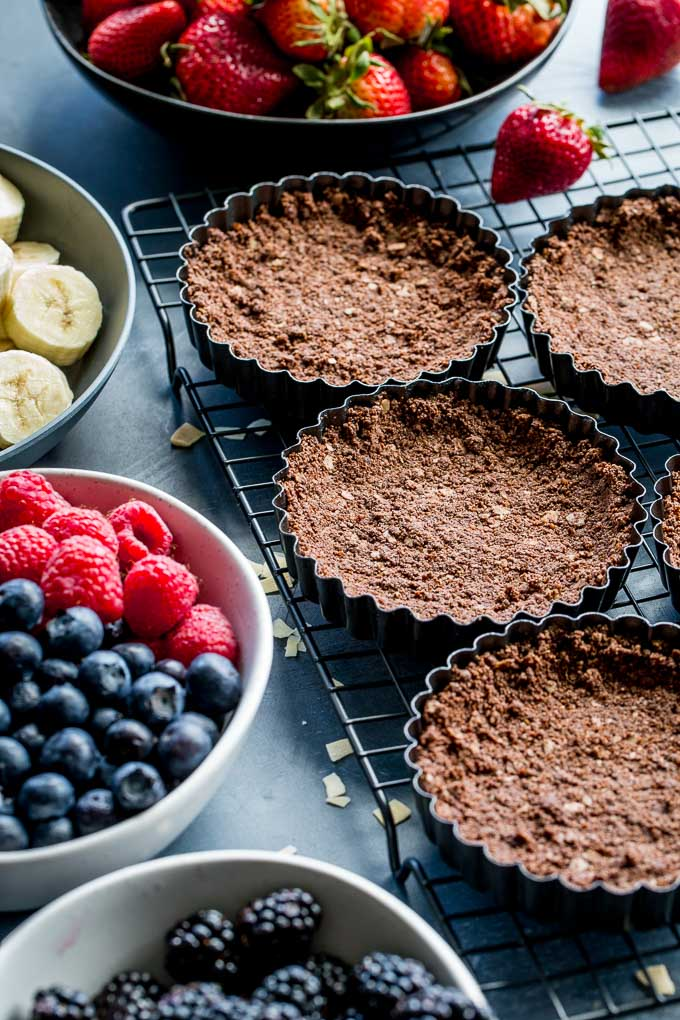 Chocolate tart shells cooling on a wire rack, next to bowls of fruit.