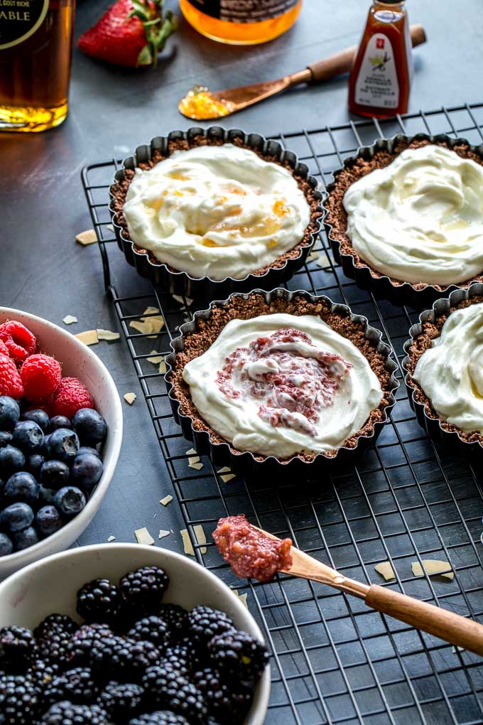 Tart shells filled with yogurt on a wire rack.