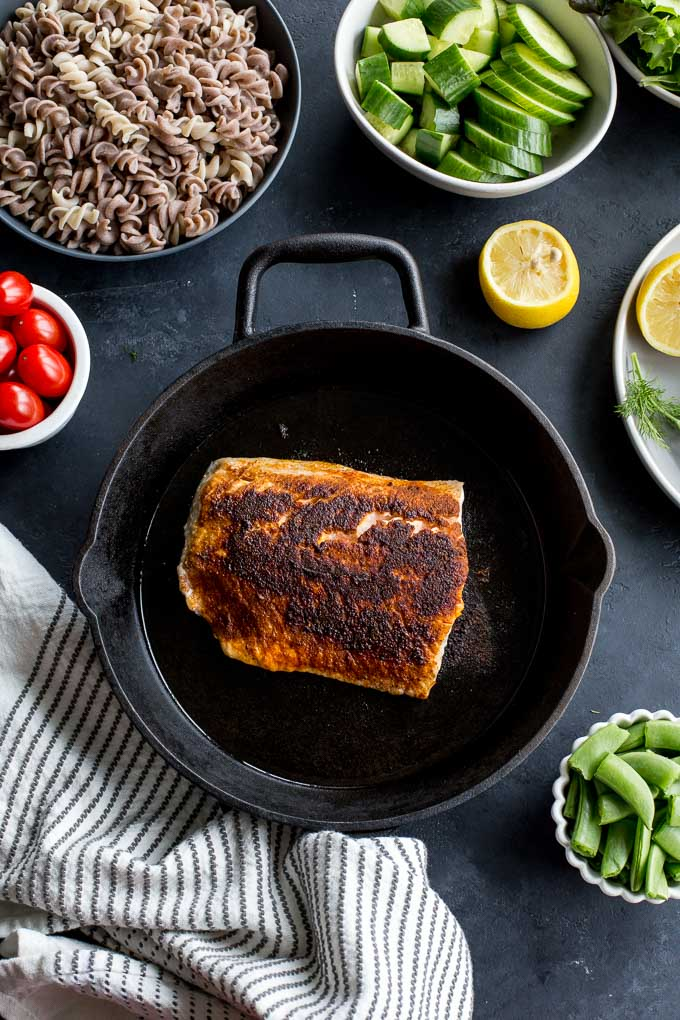 Overhead view of seared salmon in a cast iron pan on a dark surface and surrounded by other salad ingredients.
