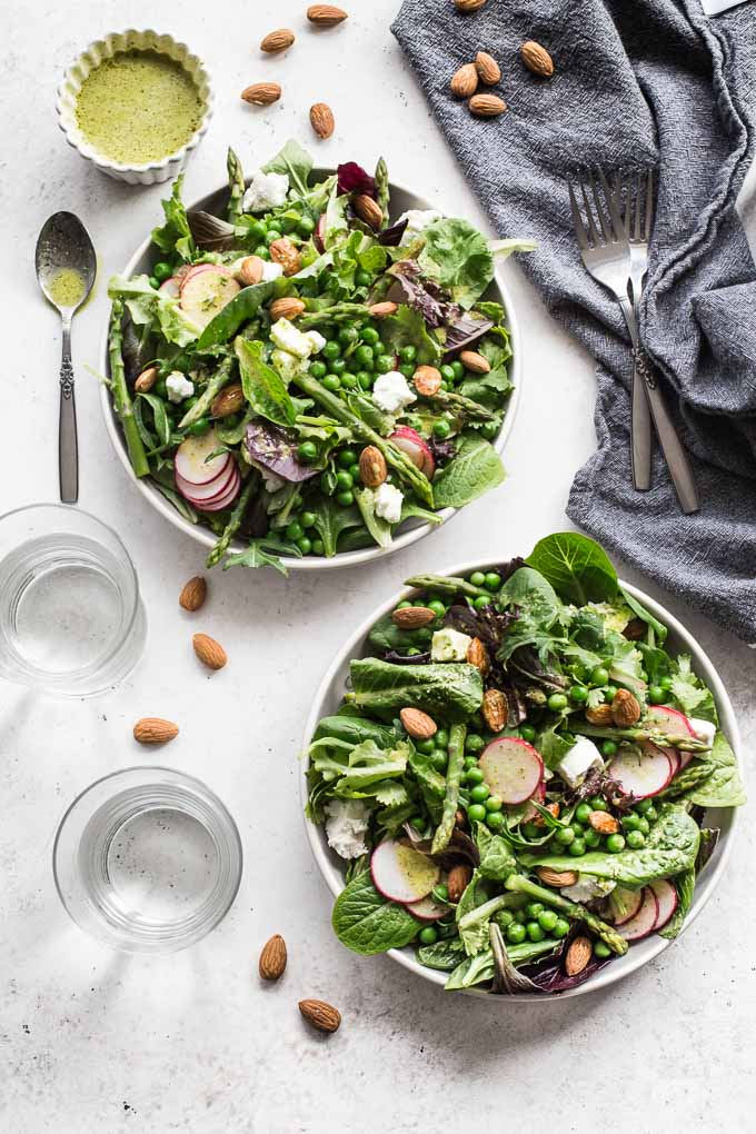 Overhead view of two plates of spring salad on a white surface, next to napkins, forks and glasses of water.