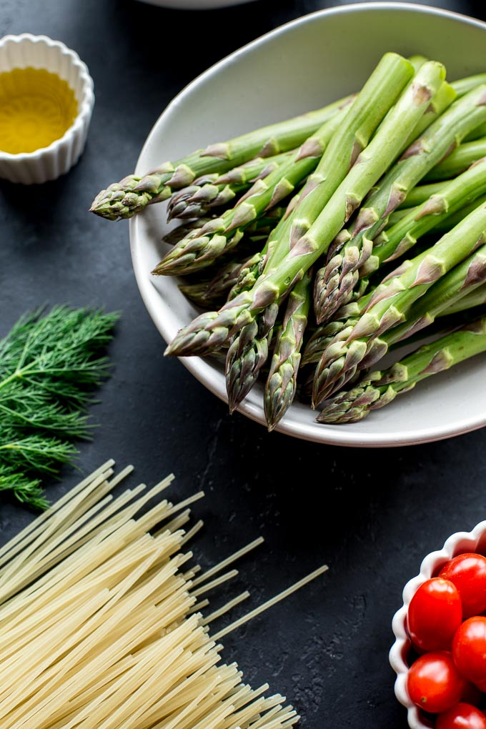 Up-close view of asparagus spears in a white bowl.