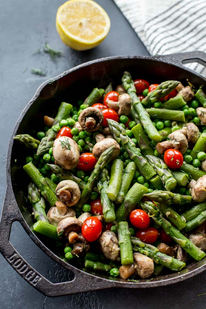 Asparagus, peas and other vegetables in a skillet on a dark surface.