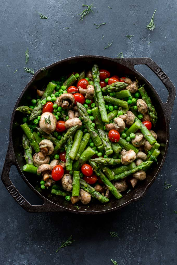 Overhead view of asparagus, peas and vegetables in a skillet on a dark surface.