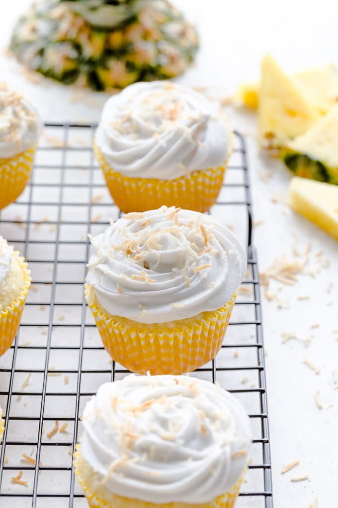 Pineapple coconut cupcakes arranged on a wire rack.