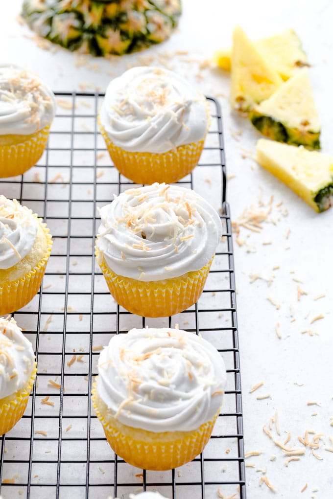 Pineapple coconut cupcakes on a wire rack with pineapple slices in the background.