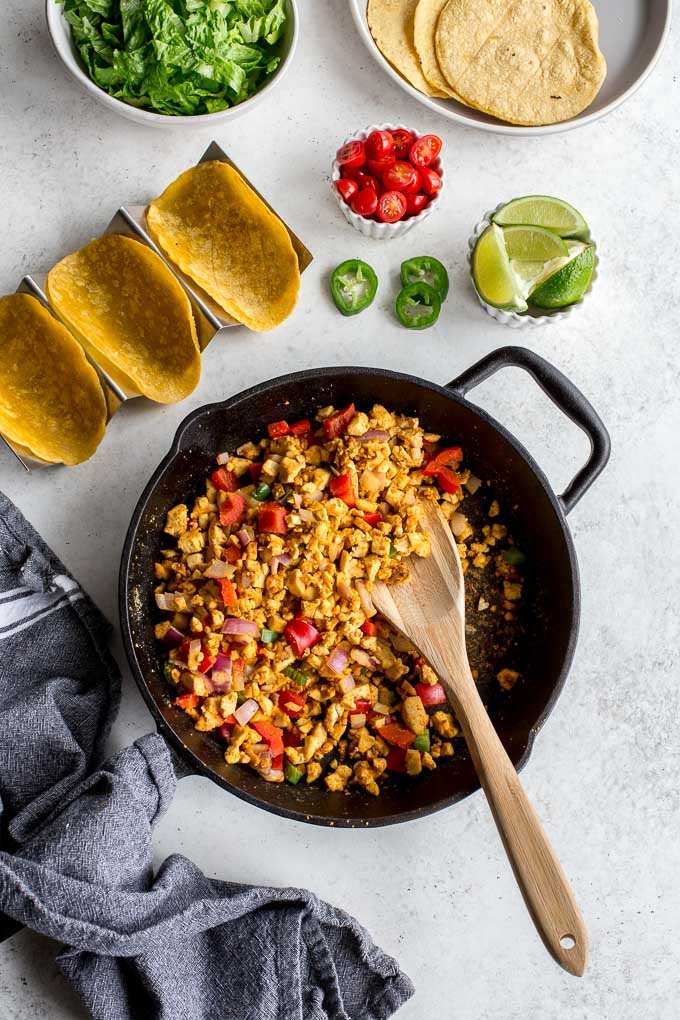Overhead view of spicy tofu scramble in a skillet, with the other taco ingredients surrounding it.