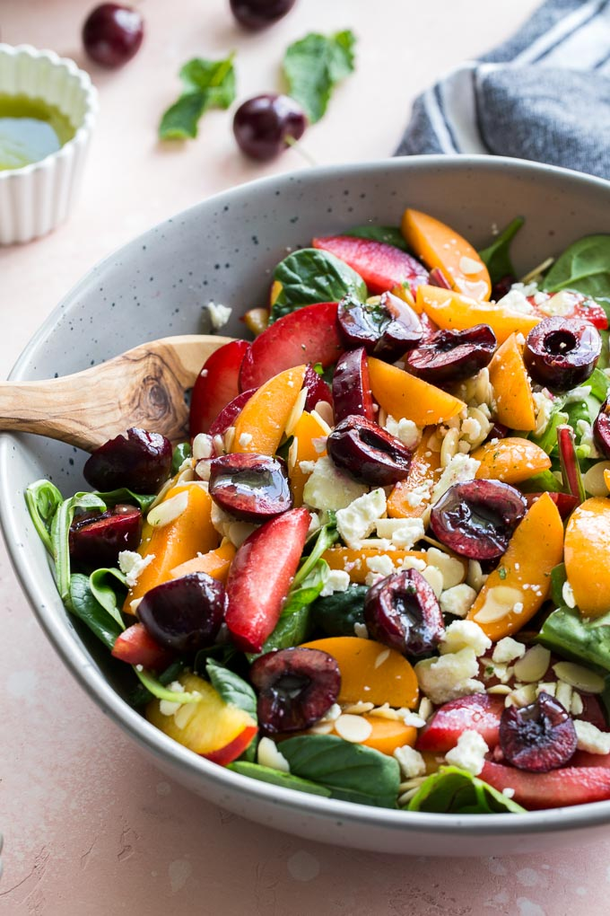 Up-close view of stone fruit salad in a grey bowl.