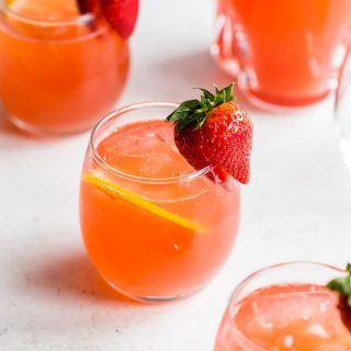 Glasses of strawberry rhubarb gin fizz arranged on a light coloured surface.