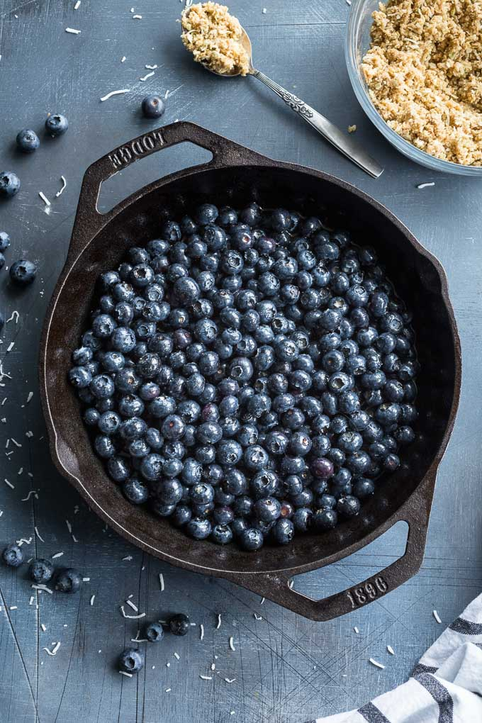 Overhead view of blueberries in a cast iron skillet.