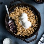 Overhead view of blueberry cardamom crisp in a cast iron skillet on a dark surface.