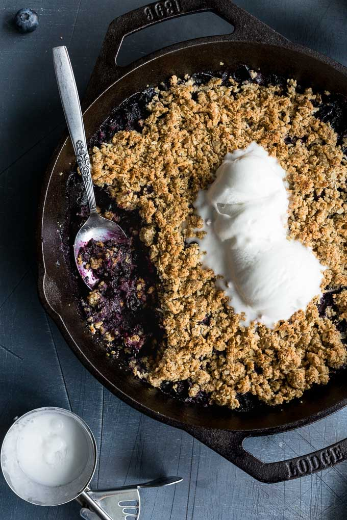 Up-close view of blueberry cardamom crisp in a cast iron skillet and topped with ice cream.