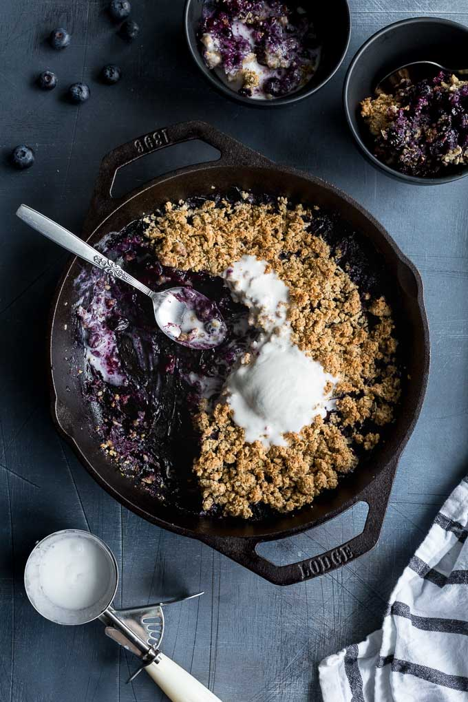 Overhead view of a half eaten blueberry crisp in a cast iron skillet