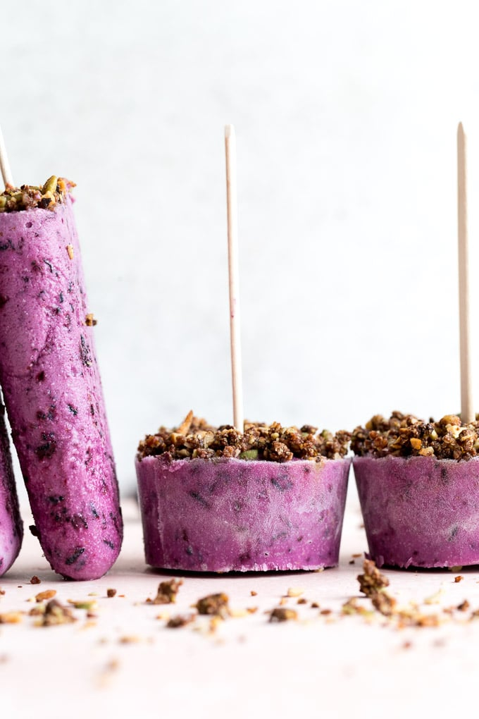 Up-close side view of blueberry goat cheese ice cream bars and cups.