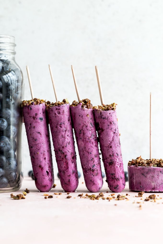 Side view of blueberry goat cheese ice cream bars propped up next to a jar of blueberries.