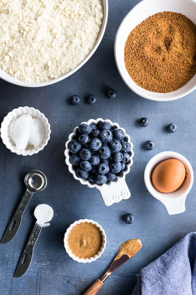 Ingredients to make a blueberry skillet cookie arranged on a dark surface.