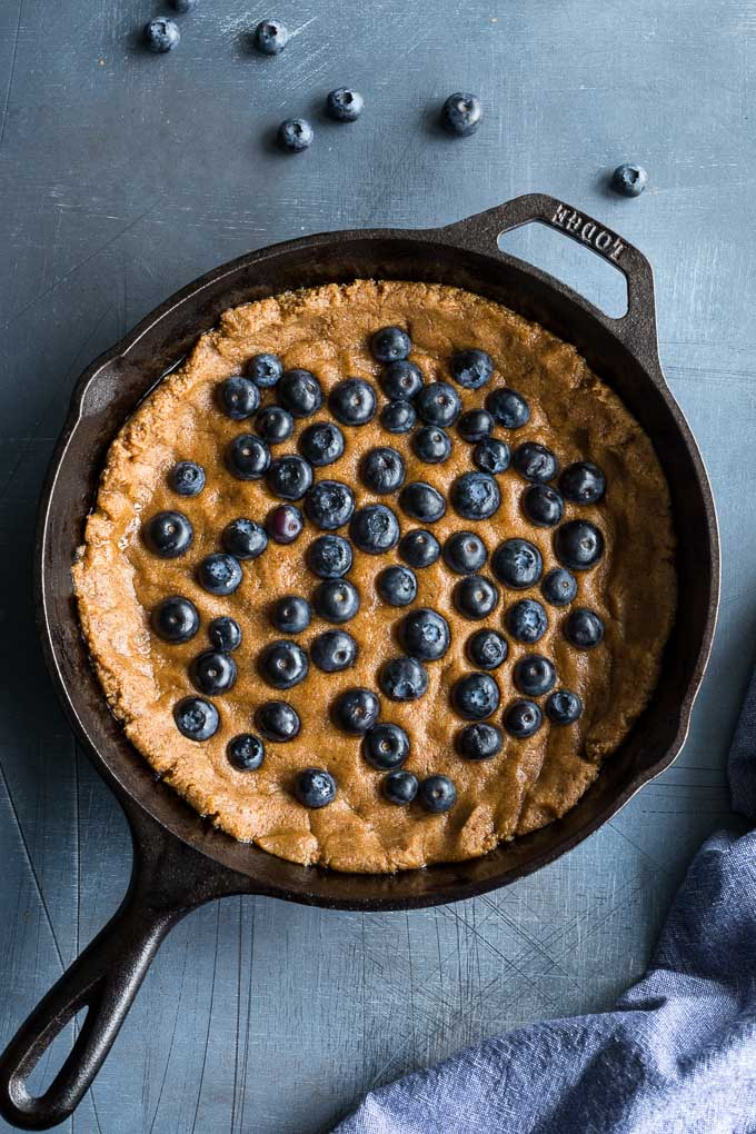 Cookie dough pressed into a cast iron skillet and topped with blueberries.