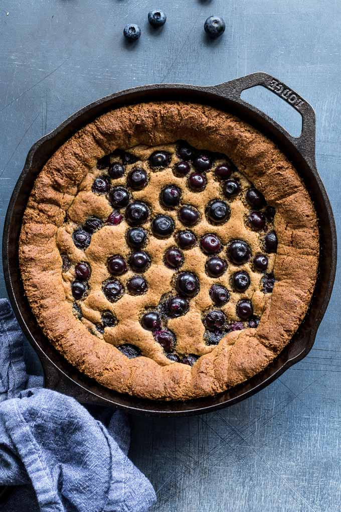 Overhead view of a blueberry skillet cookie baked up in a cast iron pan.