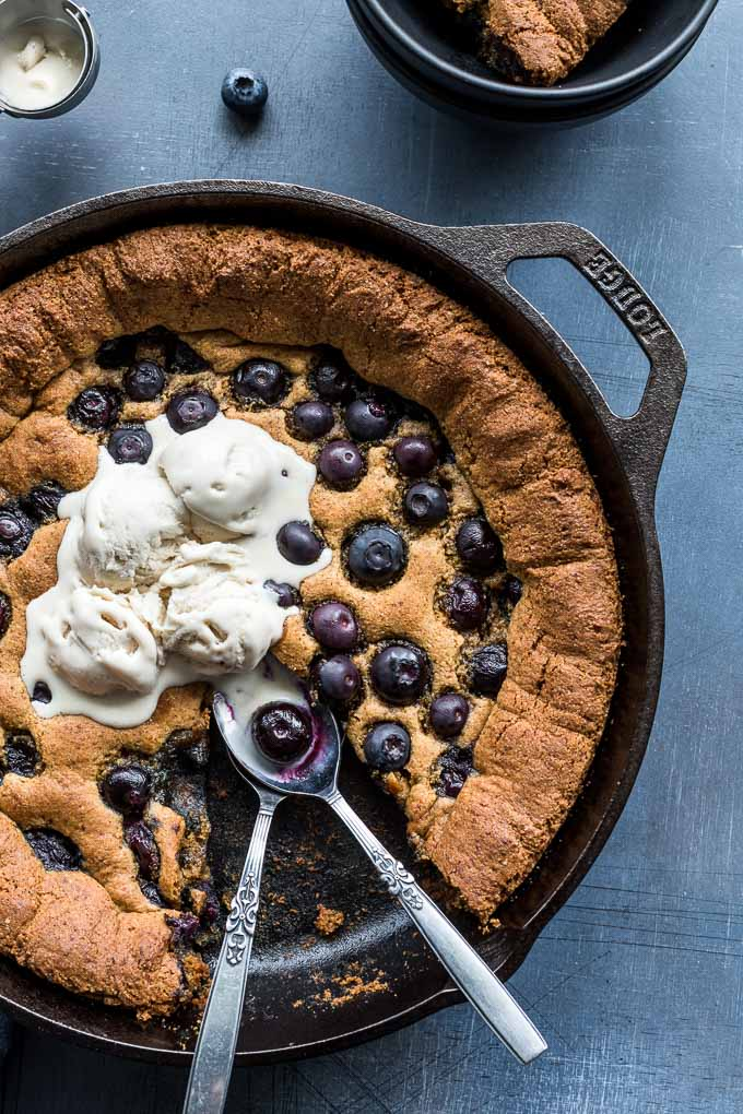 Up-close view of blueberry skillet cookie topped with ice cream and two spoons in the skillet.