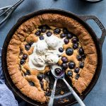 Overhead view of blueberry skillet cookie topped with ice cream in a cast iron pan.