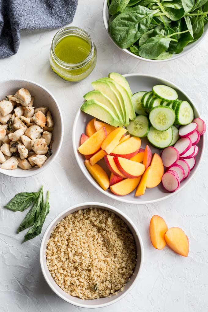 Overhead view of ingredients to make chicken and peach quinoa salad arranged on a white surface.