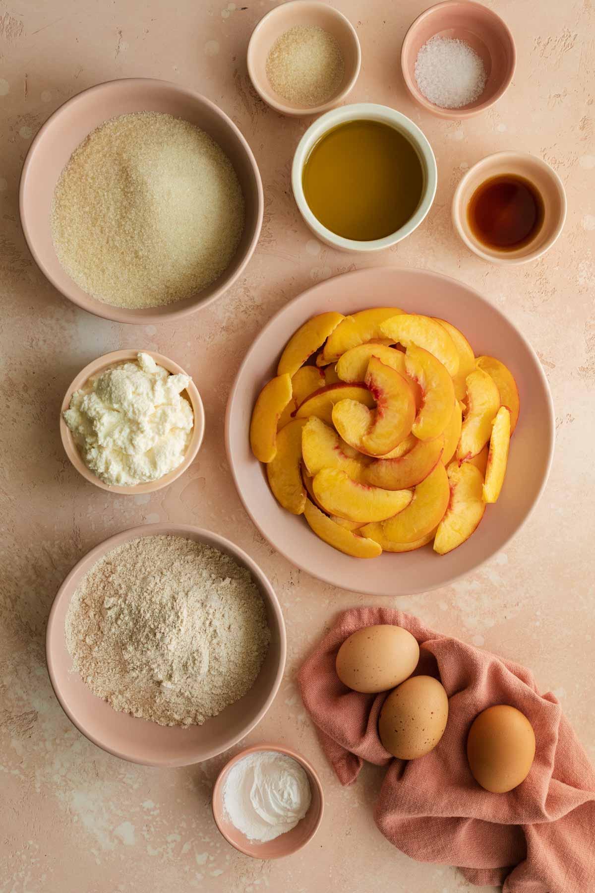 Ingredients to make peach cake arranged individually.