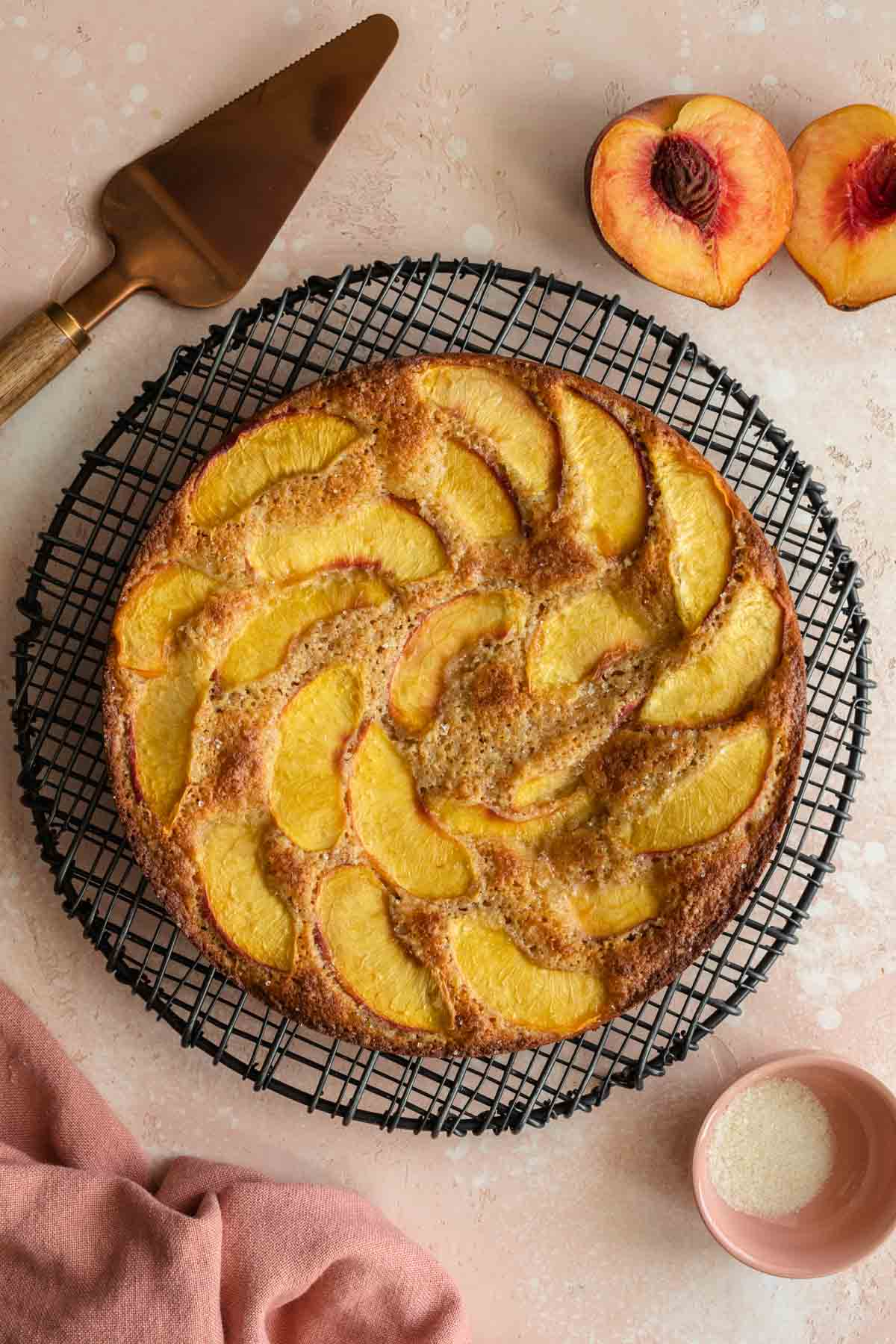 Overhead of peach cake on a round cooling rack.