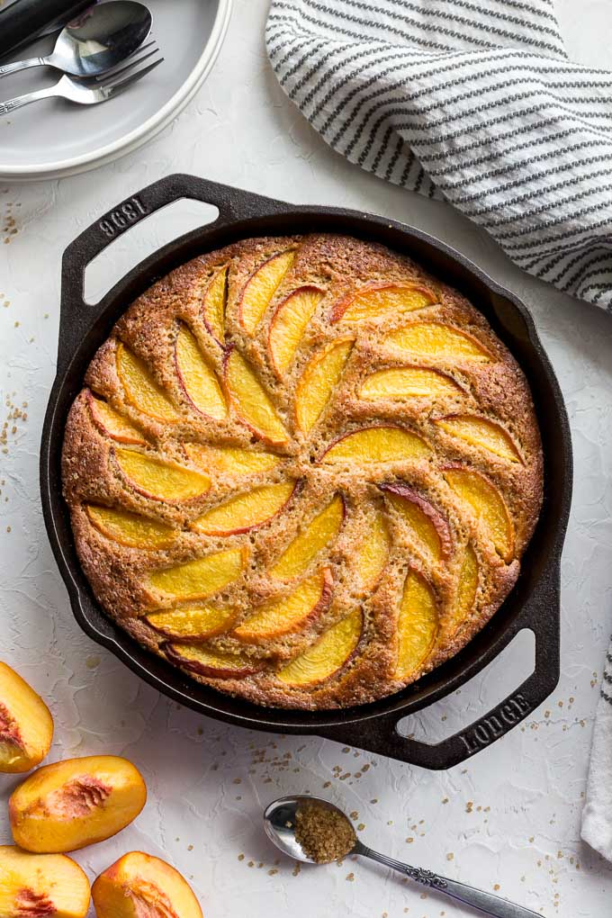 Peach ricotta skillet cake baked up in a cast iron pan.