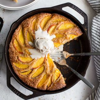 Overhead view of peach ricotta skillet cake in a cast iron pan with ice cream on top.