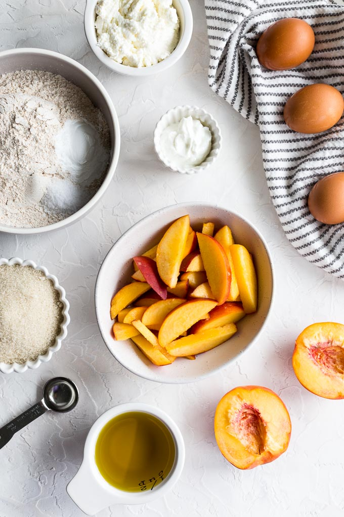Ingredients to make peach ricotta skillet cake arranged on a white surface.